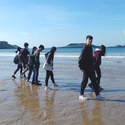 Students on the shore of Rhossili Beach